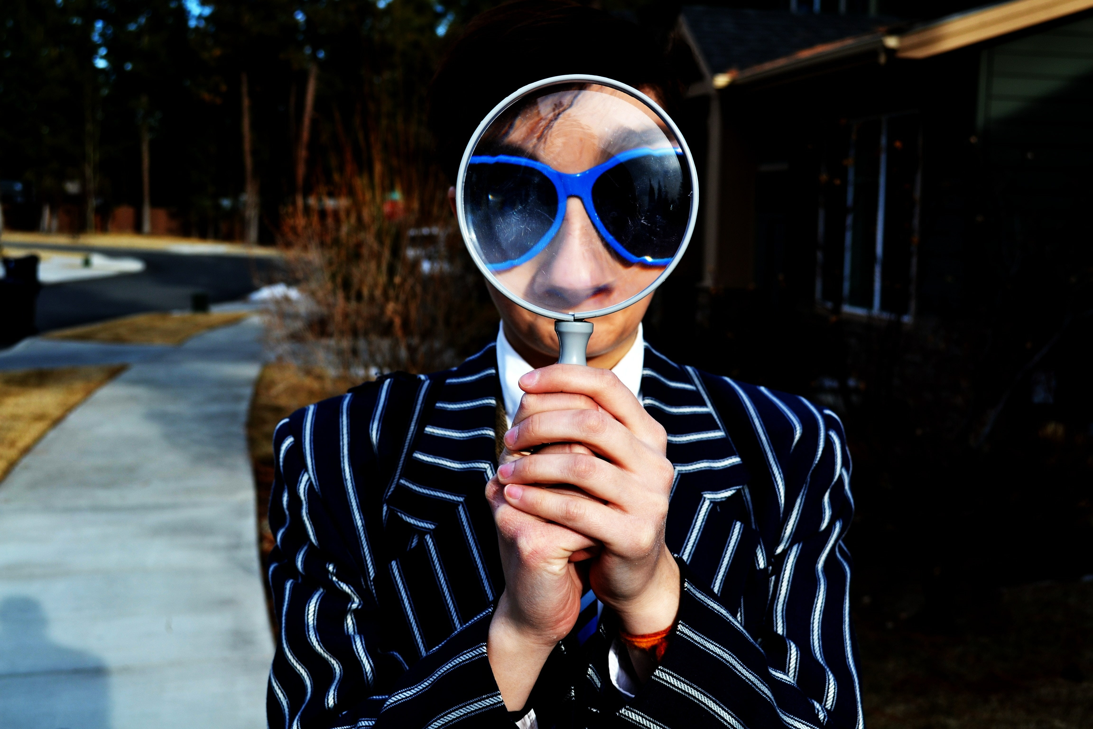 A man in a suit wearing blue glasses holding a magnifying glass up to his face.