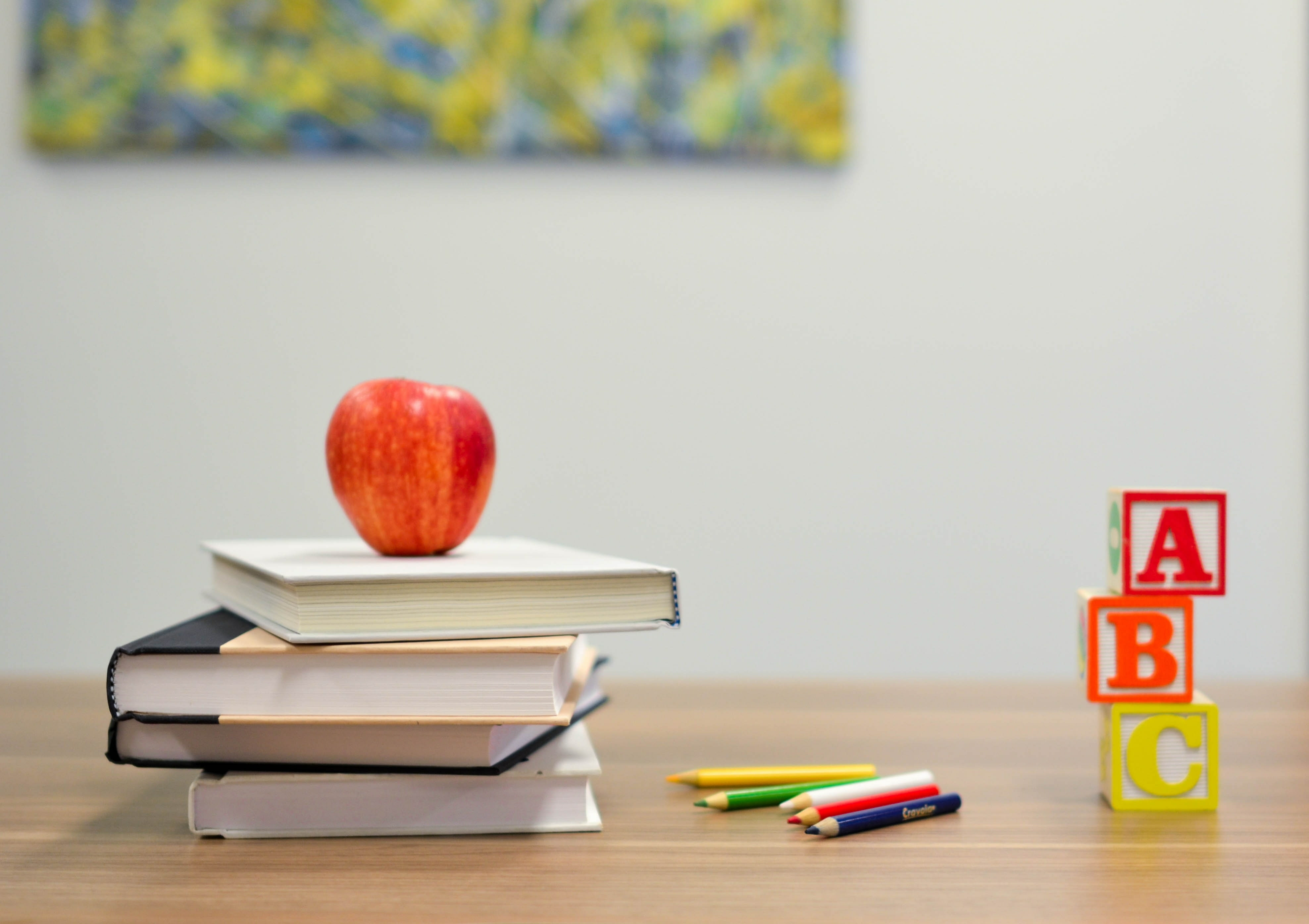 A red apple sitting on top of three books with colorful wooden alphabet blocks on the right.