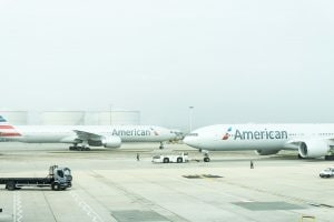 Two American Airlines planes sitting on the runway.