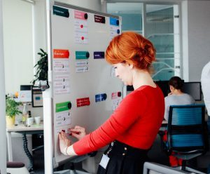 a young red headed woman creates a board to manage her campaigns