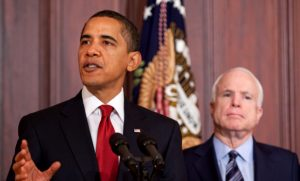 Barack Obama giving a speech with John McCain in the background.