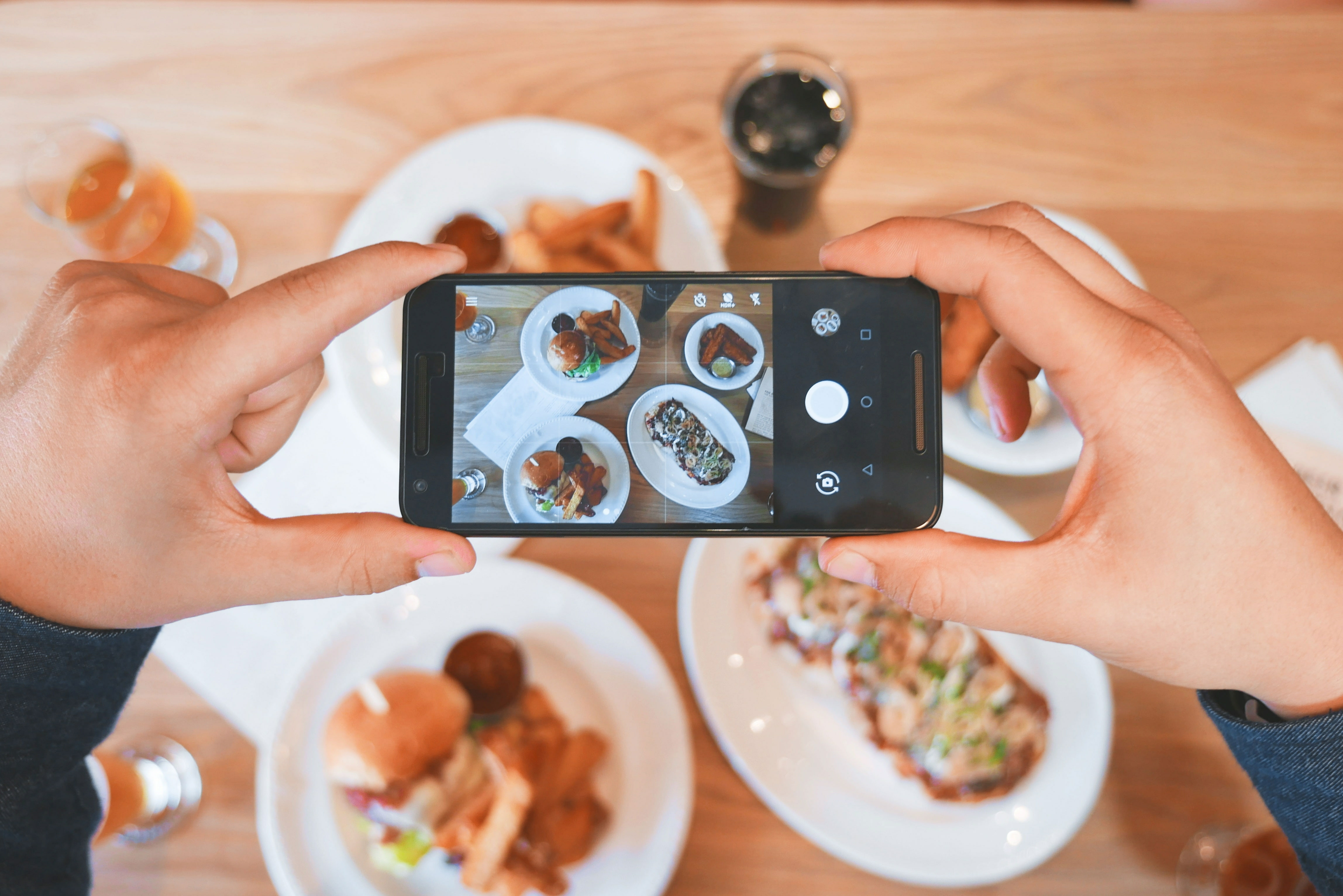 Someone taking a photo of food on white plates.