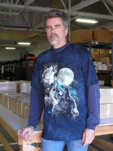 Man wearing a shirt with three wolves howling at the moon.