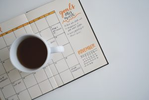 A cup of coffee next to a goal setting calendar on a desk.