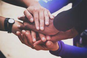 a pile of multiracial hands come together symbolizing teamwork