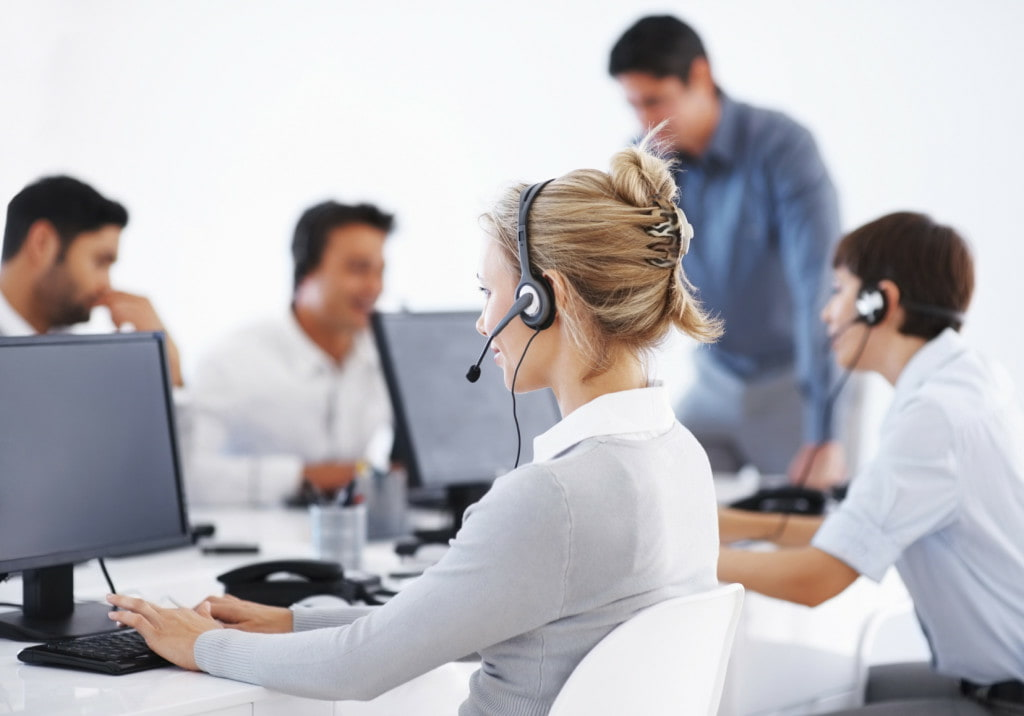 Business woman wearing headset working on computer with colleagues