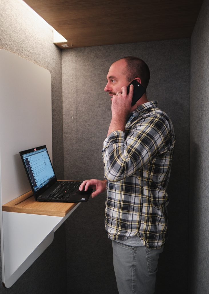 man talks on phone in a makeshift phone booth with laptop stand and laptop open