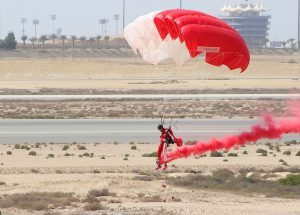 a man flying a parachute lands safely on the ground