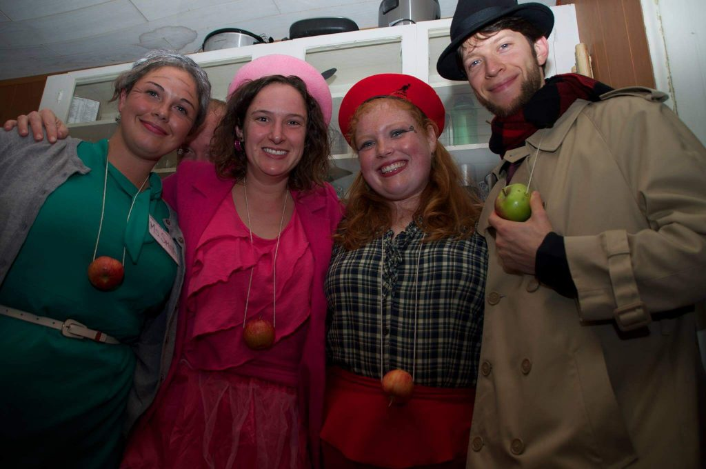 four people pose with apples for a costume