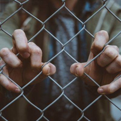 two hands through a chain link fence