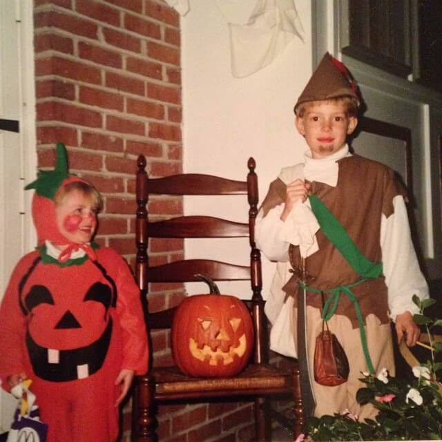 two young boys, one dressed as a pumpkin and one as robin hood for halloween