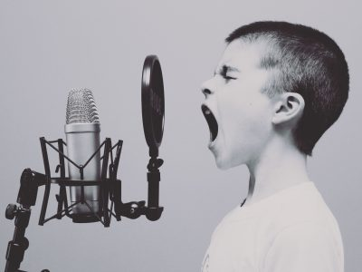 kid at microphone for brand voice blog