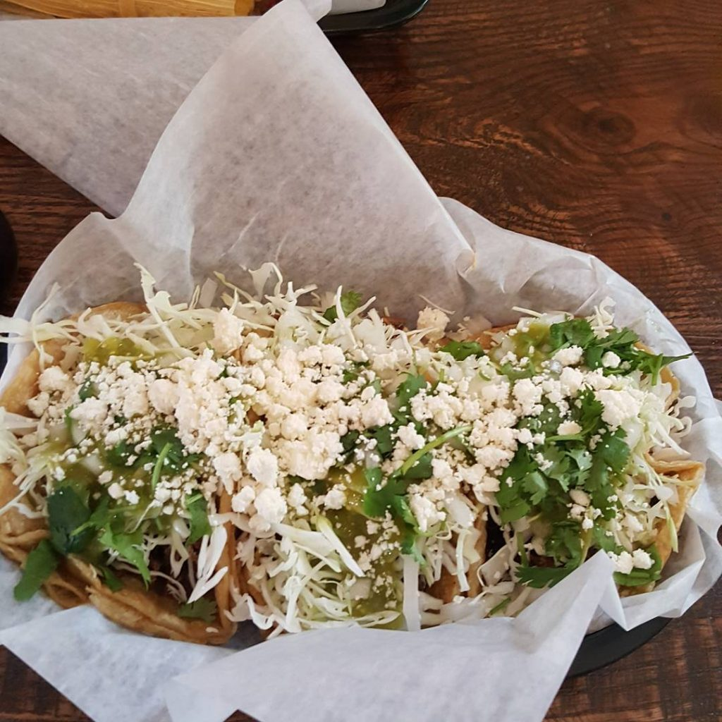 Three of the best tacos in traverse city with cotija and cabbage on top.