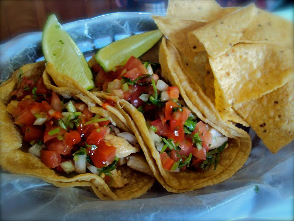 Two fresh tacos with salsa and a lime in a basket with tortilla chips.