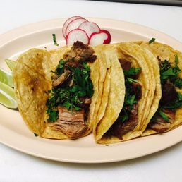 Three tacos on a white platter with thinly sliced radishes.