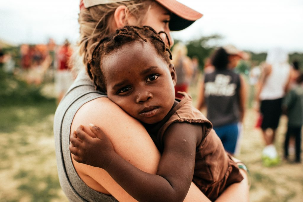 An impoverished child being held by an activist.