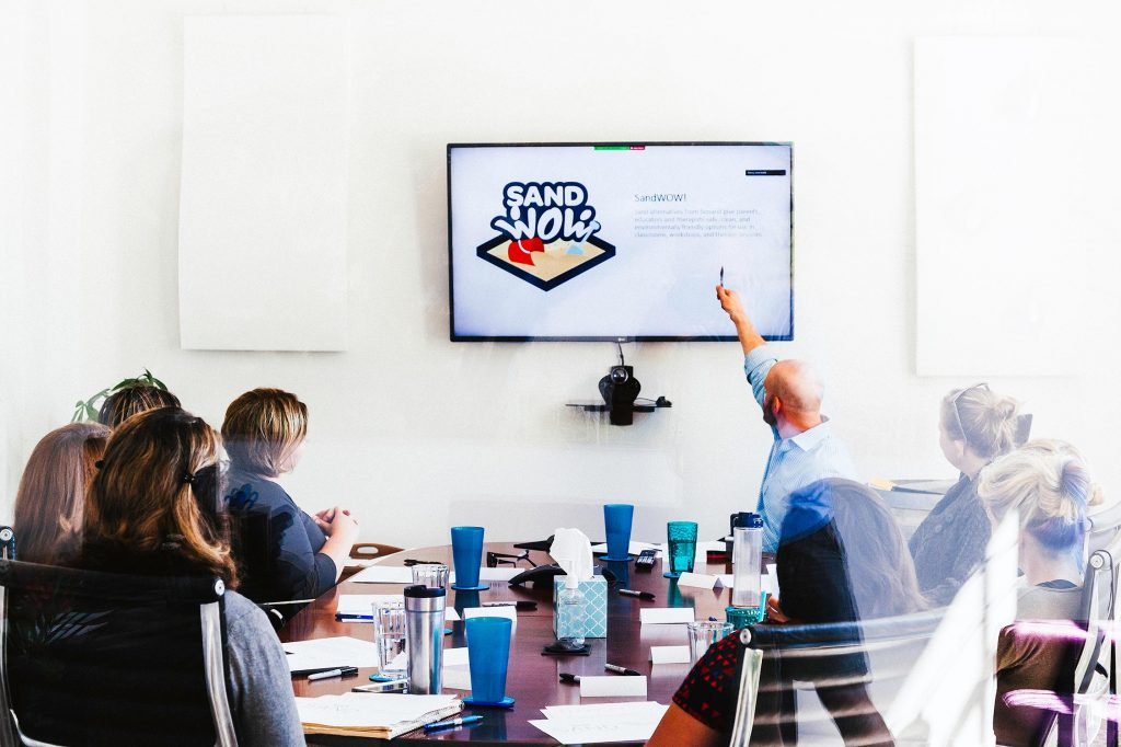 Marketing employees around a table for a SandWoW strategy meeting.