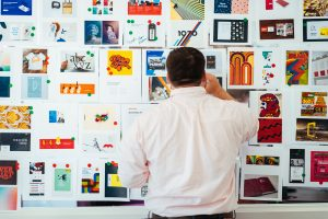 A male employee creating a collage of graphic design styles for a website redesign activity.