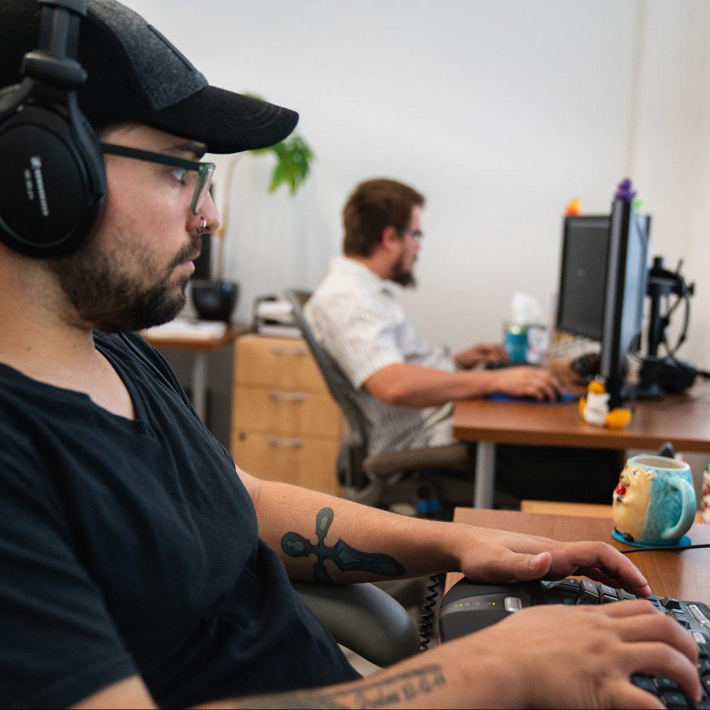 A male Oneupweb developer working at his desk.
