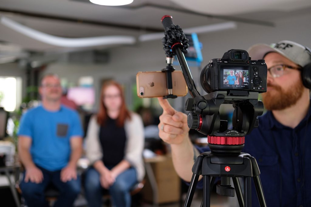 A male videographer prepares to film a man and woman for a YouTube video.
