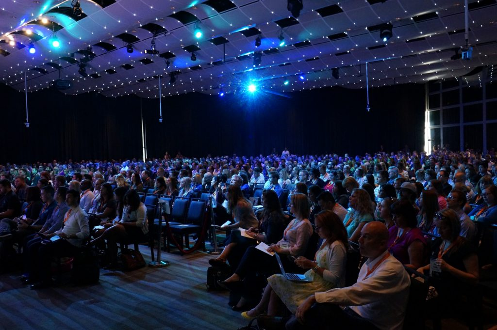 People in an auditorium listening to a speaker at Digital Summit in Detroit.