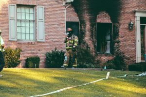 A firefighter, in full gear, walking out of a brick home that was recently on fire.