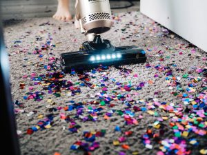 A modern vacuum cleaner vacuuming up glitter on carpet.