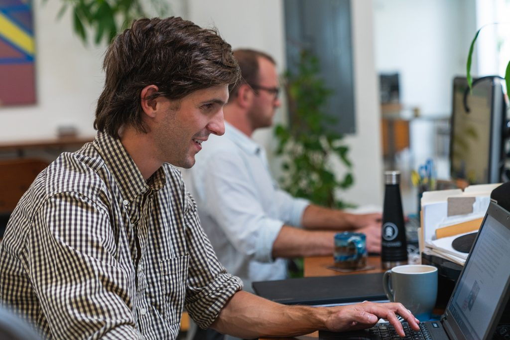 Two content marketing professionals working at their desks at the Oneupweb office.