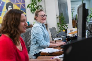 Two women smiling while working at their desks in an office.