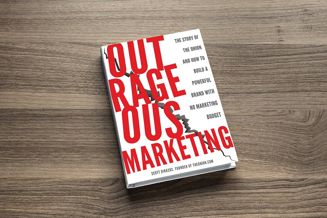Outrageous Marketing hardcover book sitting on a table.