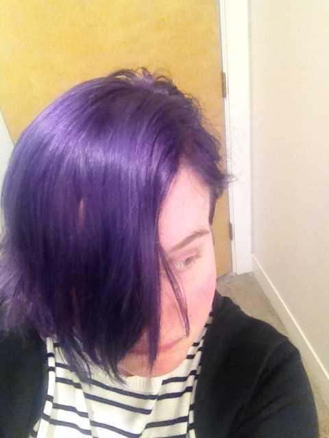 woman with very short purple hair poses for a selfie