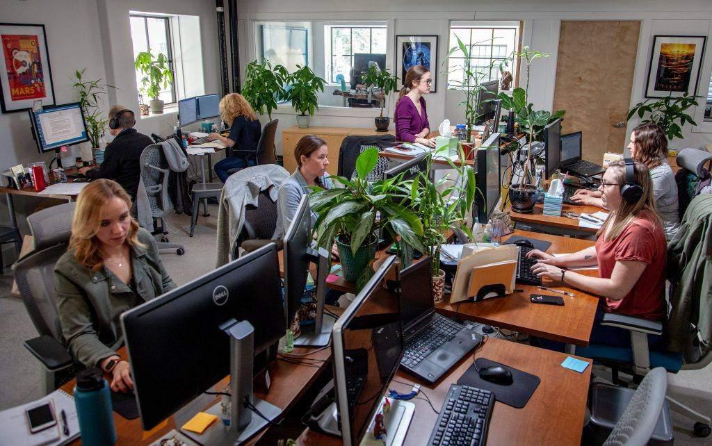 workers in an open office setting surrounded by plants