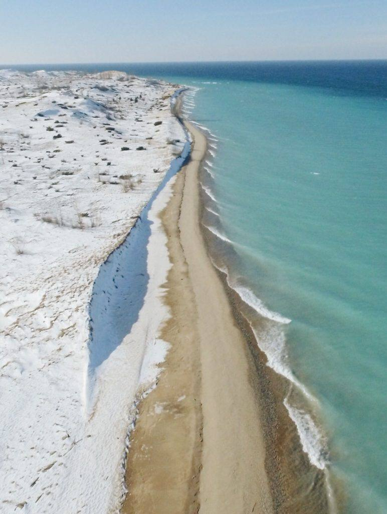 overhead shot of beach in winter with blue water