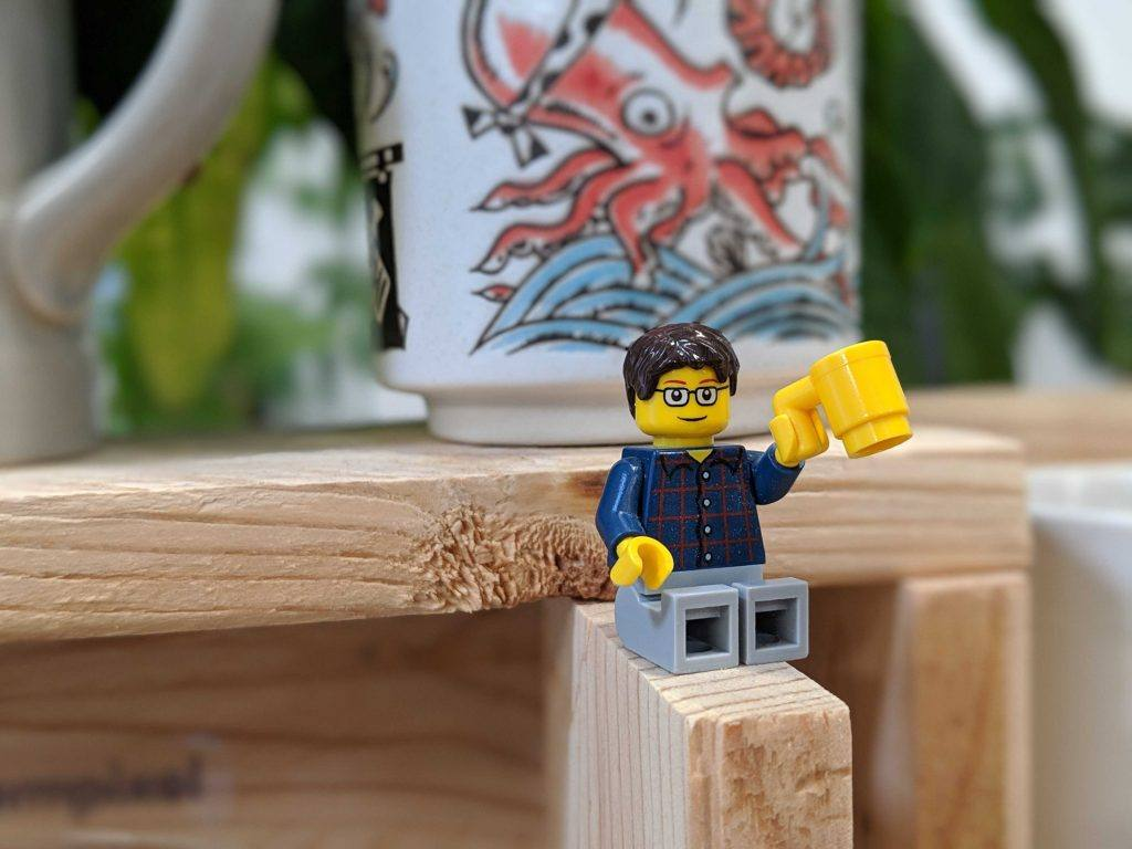 lego man sitting on a piece of wood holding a large cup