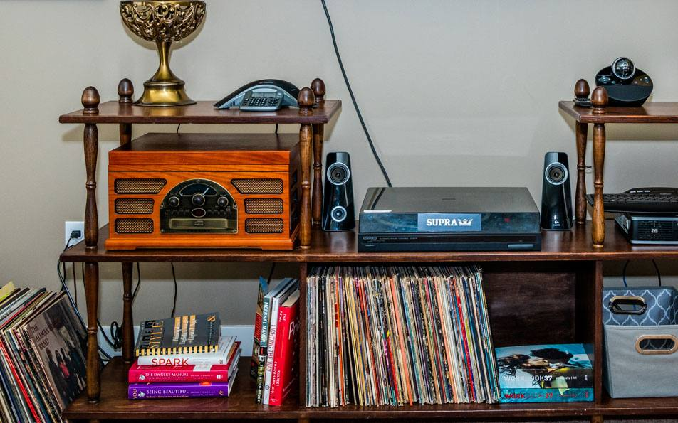 wooden shelving with lots of old records and other tech displayed on them