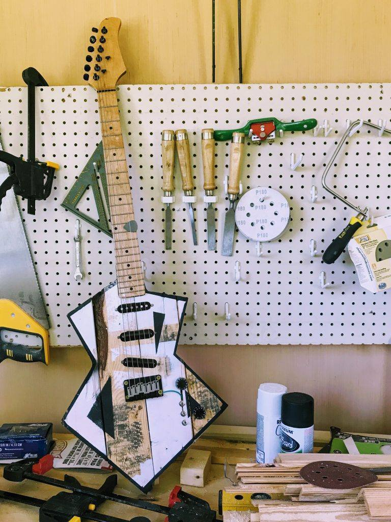 wall with tools hung on it and an electric guitar resting on the worktable below it