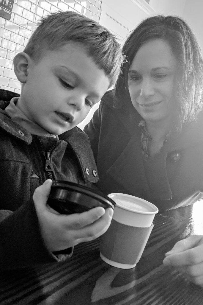 young boy opening to-go coffee cup with woman looking down on him