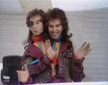 two men with mullets dressed in flashy clothes gesturing with their hands