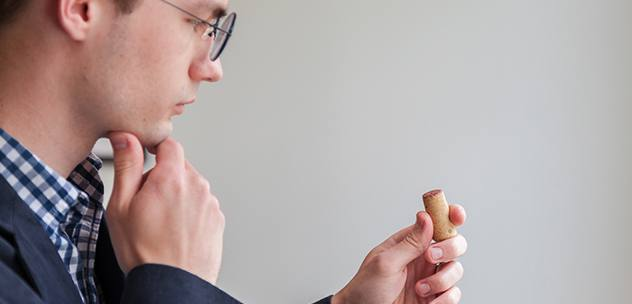 man with glasses and fingers on chin thoughtfully looking at a wine cork in his other hand