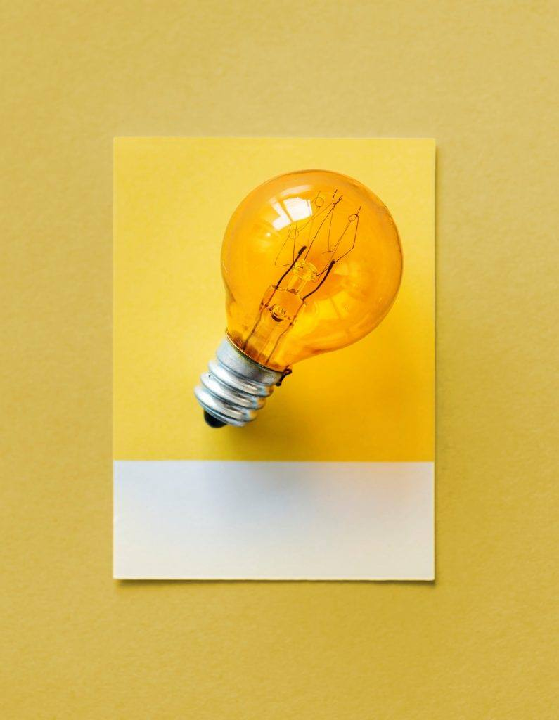 photo of lightbulb stuck to a yellow wall