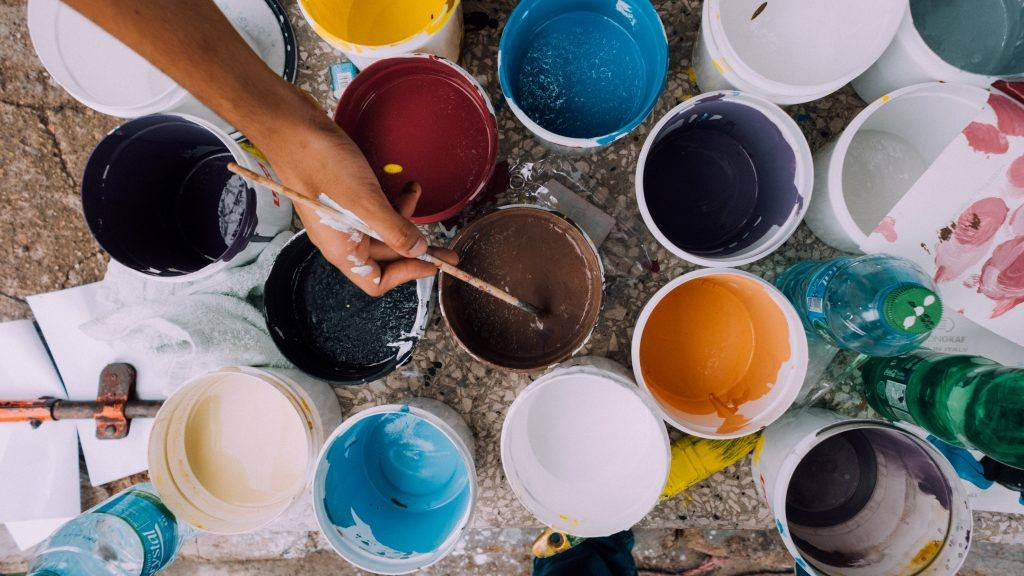 many cans of different colors of paint with one hand holding a paintbrush inside the center one