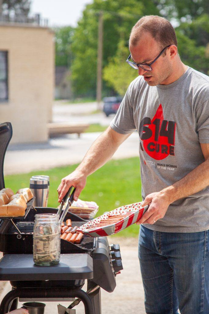 man in short sleeve t-shirt cooks hot dogs at a grill outside