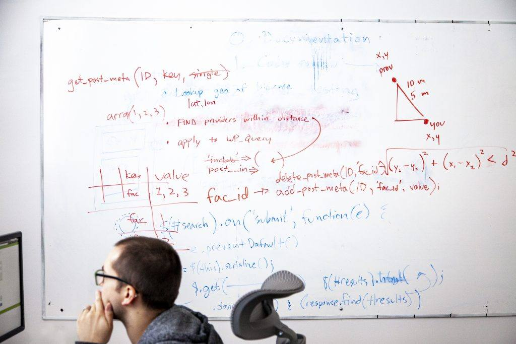 website developer in front of a whiteboard on a computer