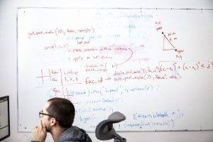 man sits at computer in front of whiteboard filled with mathematical figures