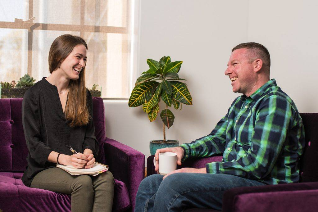man and woman sit on purple couches and laugh