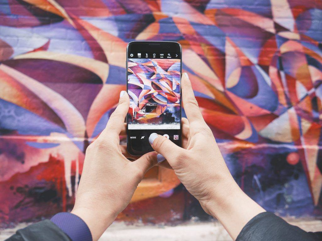 phone open to instagram photo capture screen in front of a colorful wall mural