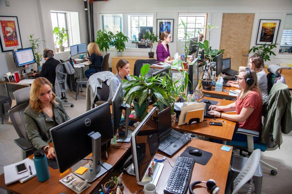 open office setting with some people at standing desks and some sitting