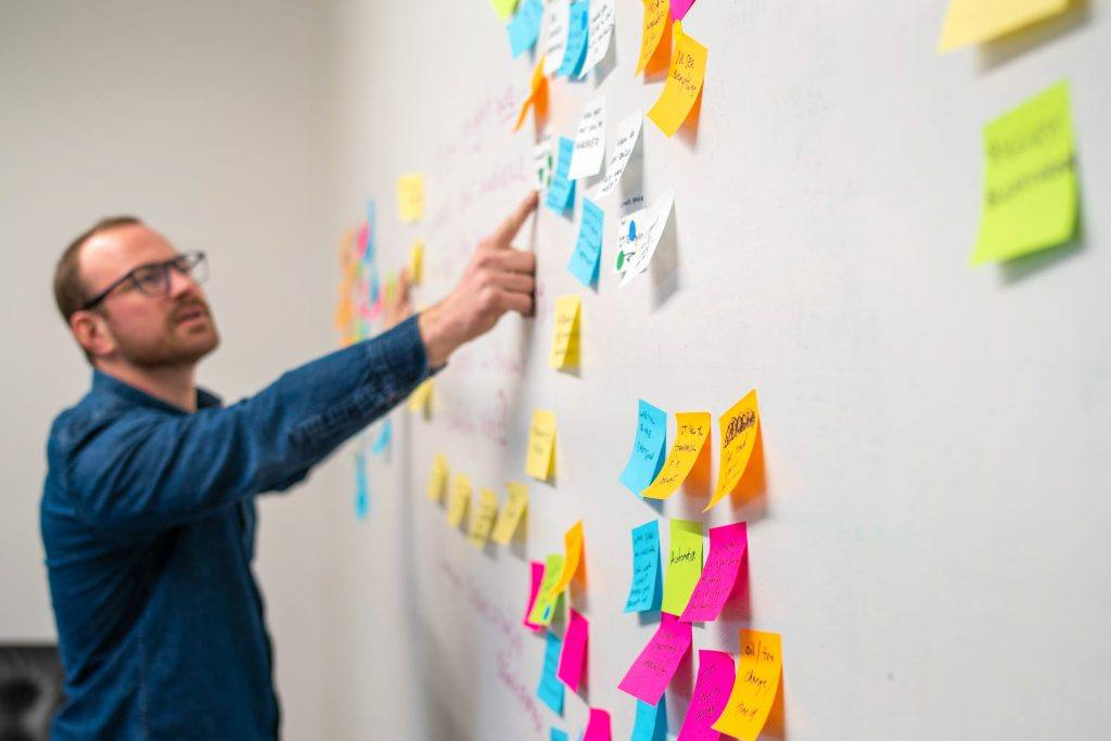 man pointing to colorful sticky notes stuck to a wall