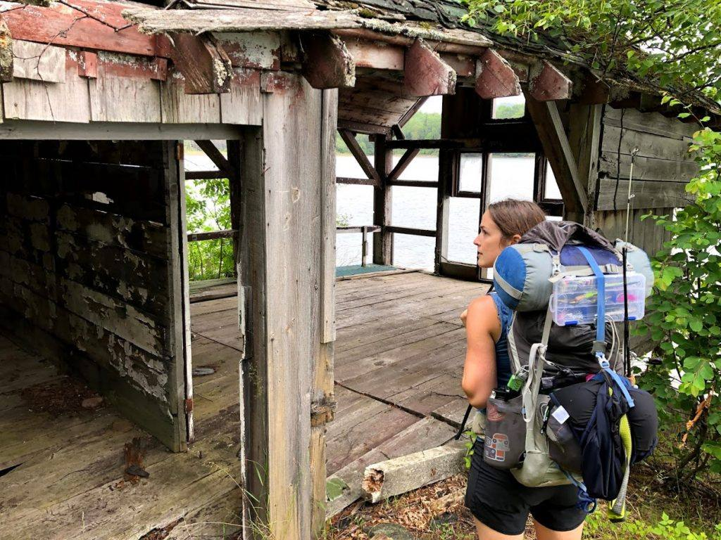 woman wearing hiking backpack walks through ruined building