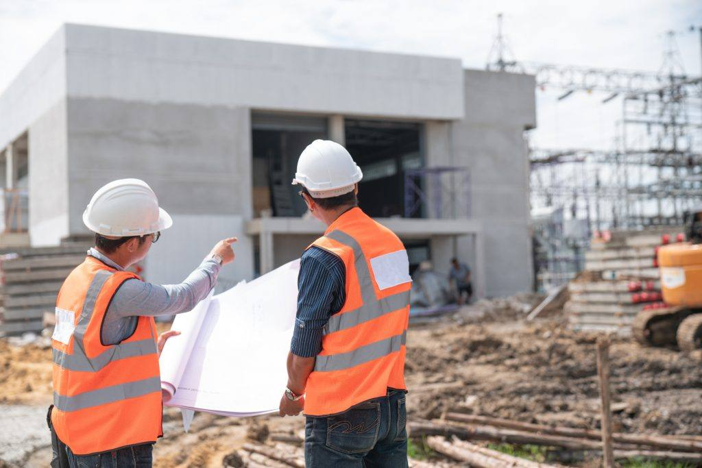 two construction workers talking and pointing